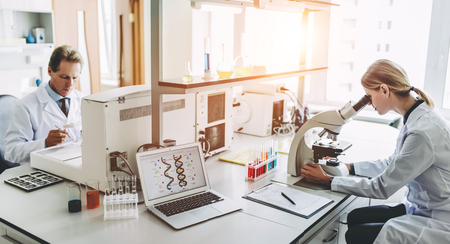 Foto de Two scientists are working in laboratory. Young female researcher and her senior supervisor are doing investigations on laboratory equipment. - Imagen libre de derechos