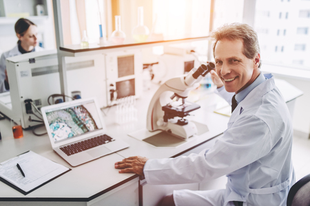 Photo pour Two scientists are working in laboratory. Young female researcher and her senior supervisor are doing investigations with microscope. - image libre de droit