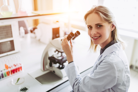 Foto de Experienced female scientist is working in laboratory. Doing investigations with microscope. - Imagen libre de derechos