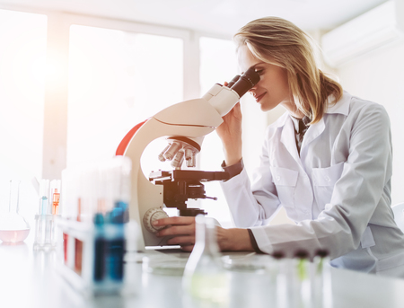 Foto de Experienced female scientist is working in laboratory. Doing investigations with microscope. - Imagen libre de derechos