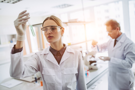 Foto de Two scientists are working in laboratory. Young female researcher and her senior supervisor are doing investigations with test tubes. - Imagen libre de derechos