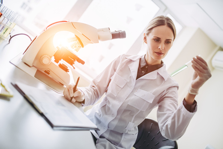 Foto de Experienced female scientist is working in laboratory. Doing investigations with microscope and test tubes. - Imagen libre de derechos