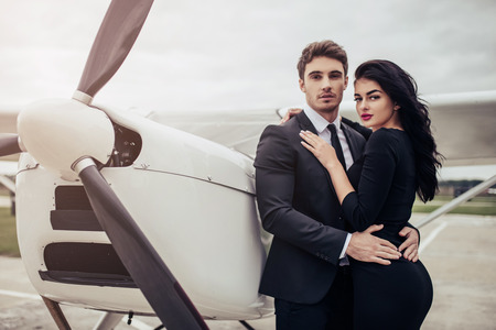 Photo for Beautiful young stylish couple in official clothes is standing near private plane. Hugging and kissing in airport in front of airplane. - Royalty Free Image