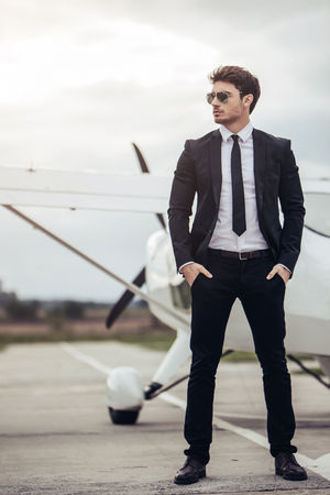 Photo pour Young handsome businessman is standing near private plane. Confident and successful man in airport. - image libre de droit