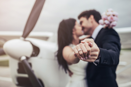 Foto per Just married! Beautiful young romantic couple is standing near private plane. Attractive woman in wedding dress and handsome man in suit are celebrating wedding day in airport near airplane. Ready for Honeymoon. Young woman is showing wedding ring. - Immagine Royalty Free