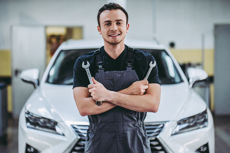 Photo pour Handsome auto service mechanic in uniform is standing on the background of car with open hood with wrench in hands. Car repair and maintenance. - image libre de droit