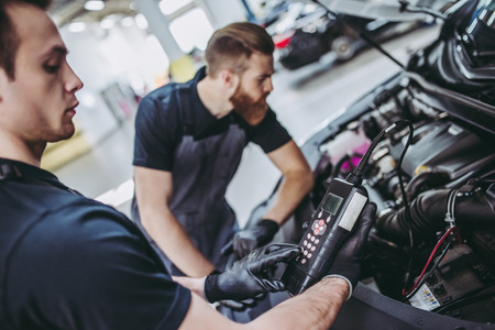 Photo for Two handsome mechanics in uniform are working in auto service. Car repair and maintenance. Performing engine diagnostics - Royalty Free Image
