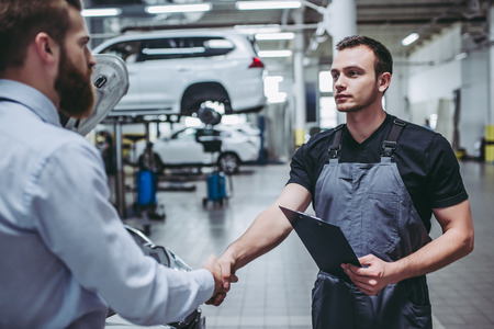 Photo for Handsome businessman and auto service mechanic are discussing the work and shaking hands. Car repair and maintenance. - Royalty Free Image