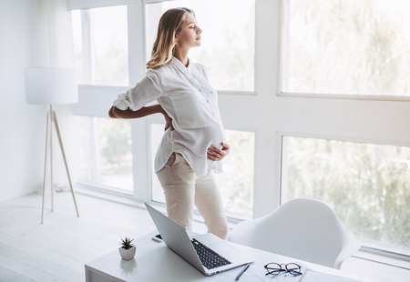 Photo pour Attractive pregnant woman is working in light modern office. Feel of tiredness on last months of pregnancy. - image libre de droit