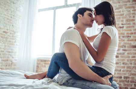 Foto de Beautiful young couple is sitting on bed in bedroom. Enjoying spending time together at home. - Imagen libre de derechos