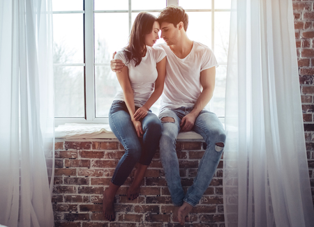 Photo pour Beautiful young couple at home. Hugging and kissing while sitting on a window sill. Enjoying spending time together. - image libre de droit