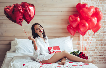 Photo pour Beautiful young woman at home. Attractive girl is sitting on bed with gift box, air baloons in shape of heart and red roses. Celebrating Saint Valentines Day. - image libre de droit
