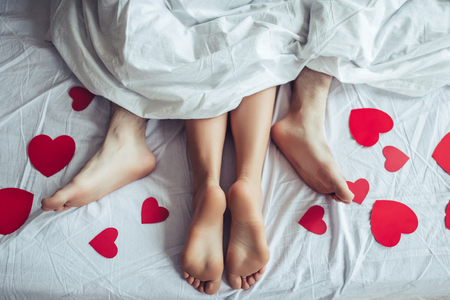 Photo pour Cropped image of young couple is lying on bed. Close up of male and female feet. Loving couple is lying on bed under blanket covered by small red paper hearts. Saint Valentines Day. - image libre de droit