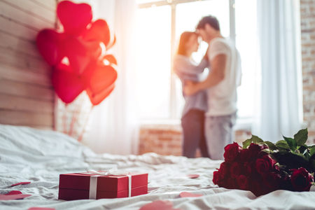 Photo pour Beautiful young couple at home. Hugging, kissing and enjoying spending time together while celebrating Saint Valentine's Day with red roses on bed and air balloons in shape of heart on the background. - image libre de droit