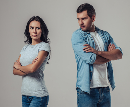 Foto de Beautiful romantic couple isolated on grey background. Standing apart from each other while being in a quarrel. - Imagen libre de derechos