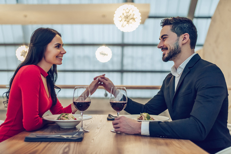 Foto de Beautiful loving couple is spending time together in modern restaurant. Attractive young woman in dress and handsome man in suit are having romantic dinner. Celebrating Saint Valentine's Day. - Imagen libre de derechos