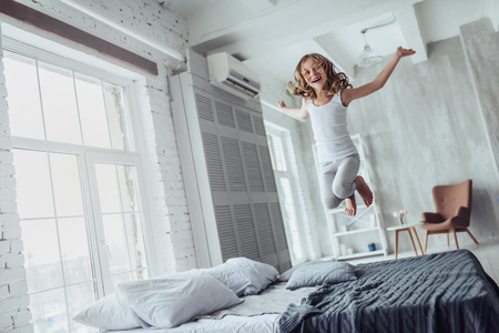 Photo for Little cute girl is jumping on bed at home in a light bedroom. - Royalty Free Image