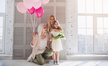 Foto de Little cute girl, her attractive young mother and charming grandmother are standing with air balloons and flowers in light room. Women's generation. International Women's Day. Happy Mother's Day. - Imagen libre de derechos