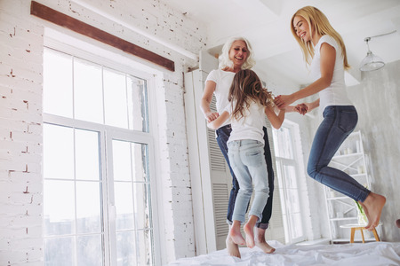 Foto de Little girl, her attractive mother and charming grandmother are having fun and jumping on bed while spending time together at home. Women's generation. International Women's Day. Happy Mother's Day. - Imagen libre de derechos
