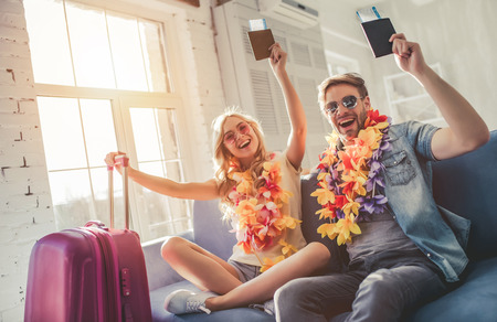 Foto de Young romantic couple wearing Hawaii accessories and sunglasses is preparing for travel at home. Sitting on sofa with passports and tickets in hands while suitcases are standing nearby - Imagen libre de derechos