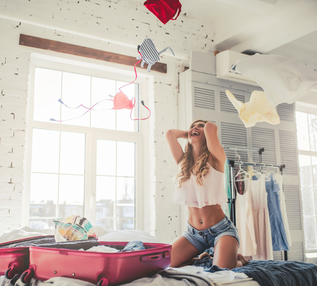 Foto de Attractive young woman is preparing for traveling while sitting on bed with big suitcase and scattering clothes up in the air. Having fun at home. - Imagen libre de derechos