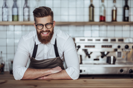 Photo for Handsome male barista is working in coffee shop. Bearded man behind the bar counter is making coffee. - Royalty Free Image