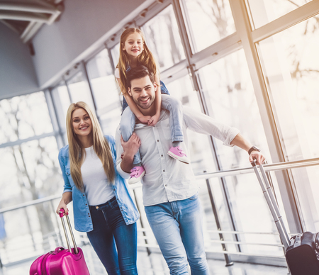 Foto de Family in airport. Attractive young woman, handsome man and their cute little daughter are ready for traveling! Happy family concept. - Imagen libre de derechos