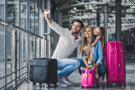 Photo pour Family in airport. Attractive young woman, handsome man and their cute little daughter are ready for traveling! Happy family concept. - image libre de droit