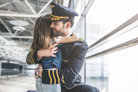 Photo pour I missed you, dad! Handsome young male pilot in uniform is meeting his little cute daughter in airport terminal. - image libre de droit