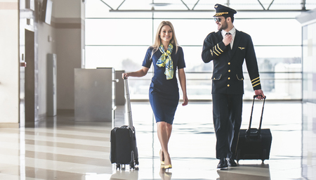 Foto de Handsome male pilot and attractive female flight attendant are walking in airport terminal together. - Imagen libre de derechos