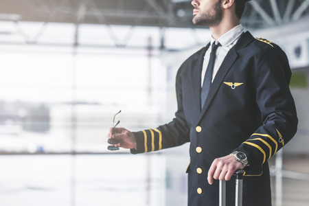Photo pour Cropped image of handsome young male pilot in the airport terminal. - image libre de droit