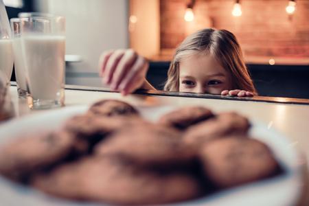 Foto de Little cute girl on kitchen is taking chocolate cookie from table. - Imagen libre de derechos