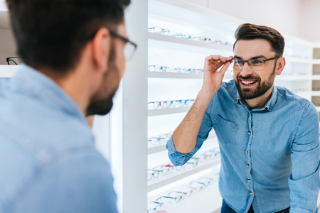 Foto de Handsome young man is choosing the most appropriate eyeglasses in modern ophthalmology clinic. - Imagen libre de derechos