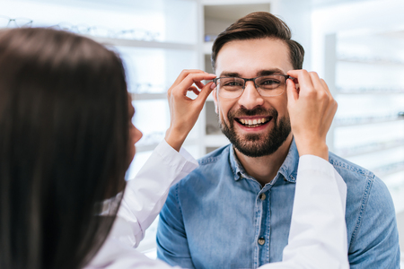 Foto de Young female doctor ophthalmologist is helping handsome man to choose the most appropriate eyeglasses. Doctor and patient in modern ophthalmology clinic - Imagen libre de derechos