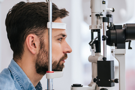 Foto de Handsome young man is checking the eye vision in modern ophthalmology clinic. Patient in ophthalmology clinic - Imagen libre de derechos