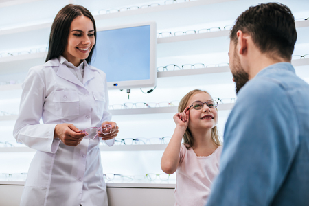 Foto de Handsome young man and his little cute daughter are choosing the best apropriate eyeglasses in modern ophthalmology clinic. Dad and daughter with doctor ophthalmologist. - Imagen libre de derechos