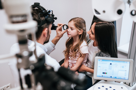 Photo for Handsome male doctor  ophthalmologist is checking the eye vision of little cute girl in modern clinic. Mom with daughter in ophthalmology clinic. - Royalty Free Image