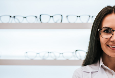 Foto de Cropped image of attractive young female doctor in ophthalmology clinic. Doctor ophthalmologist is standing near shelves with different eyeglasses. - Imagen libre de derechos