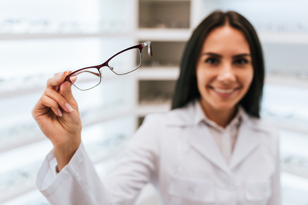 Photo pour Attractive young female doctor in ophthalmology clinic. Doctor ophthalmologist is standing near shelves with different eyeglasses. - image libre de droit