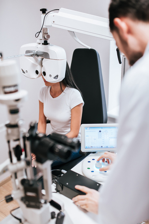 Foto de Handsome male doctor  ophthalmologist is checking the eye vision of attractive young woman in modern clinic. Doctor and patient in ophthalmology clinic. - Imagen libre de derechos