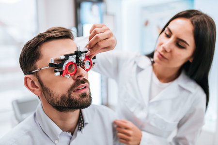 Foto de Attractive female doctor  ophthalmologist is checking the eye vision of handsome young man in modern clinic. Doctor and patient in ophthalmology clinic. - Imagen libre de derechos