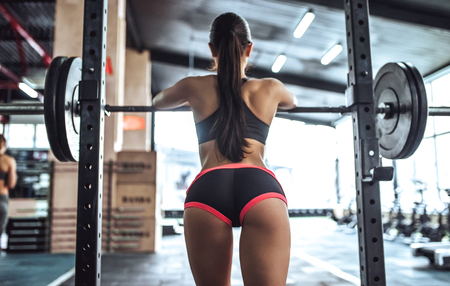 Photo pour Attractive young sporty woman is working out in gym. Cross fit training. Muscular woman is squatting with barbell - image libre de droit