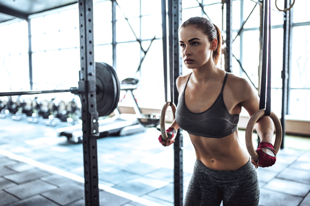 Foto de Attractive young sporty woman is working out in gym. Cross fit training. Muscular woman with athletics rings - Imagen libre de derechos