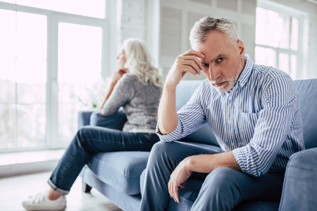 Photo for Senior couple at home. Handsome old man and attractive old woman are having relationship problems. Sitting on sofa together and looking to opposite sides. - Royalty Free Image