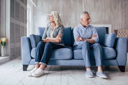 Photo pour Senior couple at home. Handsome old man and attractive old woman are having relationship problems. Sitting on sofa together and looking to opposite sides. - image libre de droit