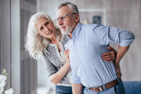 Photo pour Senior couple at home. Handsome old man is having back pain and his attractive old woman supports him. - image libre de droit