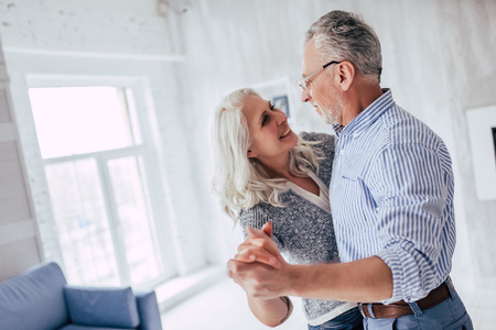 Photo pour Love lives forever! Senior couple at home. Handsome old man and attractive old woman are enjoying spending time together while dancing. - image libre de droit