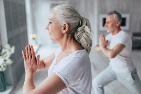 Foto de Senior couple is doing fitness training at home. Doing yoga together. Healthy lifestyle concept. - Imagen libre de derechos