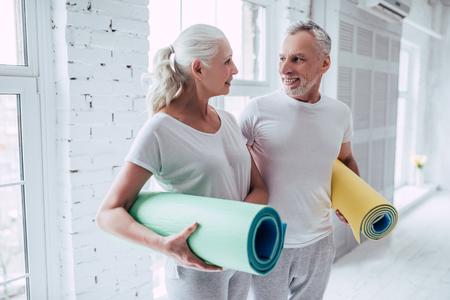 Foto de Senior couple is doing fitness training at home.Standing with fitness yoga carpets. Healthy lifestyle concept. - Imagen libre de derechos