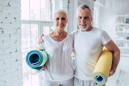 Foto de Senior couple is doing fitness training at home.Standing with fitness yoga carpets. Healthy lifestyle concept. - Imagen libre de derechos